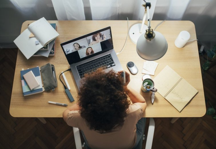 A woman sitting at her home office and talking in a meeting using her laptop.