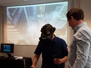 Man wearing a VR headset standing on a plank