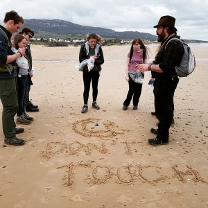 People standing on a beach looking at a jelly fish. The words Do Not Touch are written in the sand.