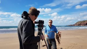 A film crew on a beach with a man holding seaweed