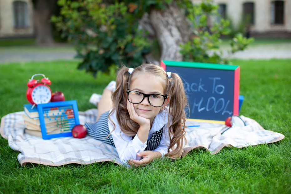 Cute smiling schoolgirl sitting on grass with lunch, books near the school.