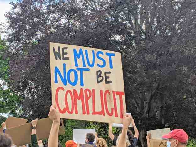 A person is holding a sign that reads We must not be complicit while attending a small town rally for Black Lives Matter