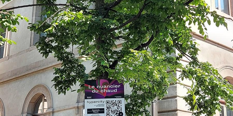 arbre avec un panneau devant un bâtiment