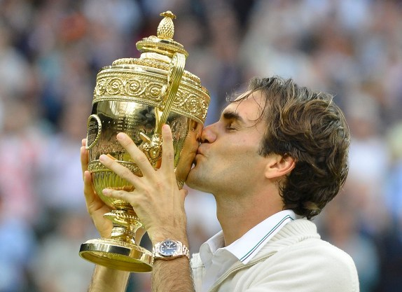 Roger Federer of Switzerland kisses the winners trophy after defeating Andy Murray of Britain in their men's singles final tennis match at the Wimbledon Tennis Championships in London July 8, 2012. REUTERS/Toby Melville (BRITAIN - Tags: SPORT TENNIS TPX IMAGES OF THE DAY)