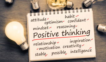 Positive Thinking factor concept on notebook with light bulbs