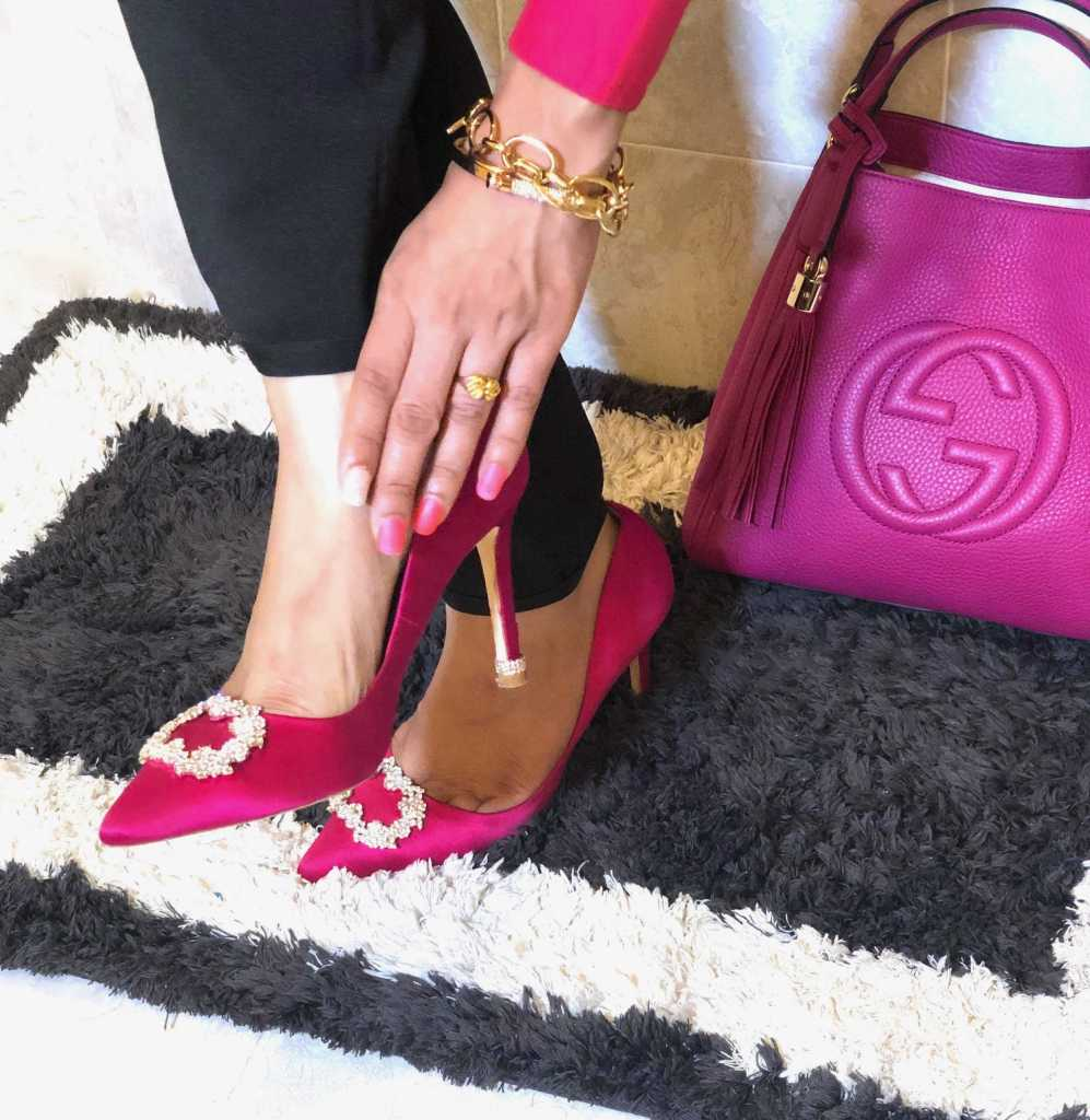 beautiful pink pumps in feet. touching one foot by hand while Gucci handbag is sitting at one side