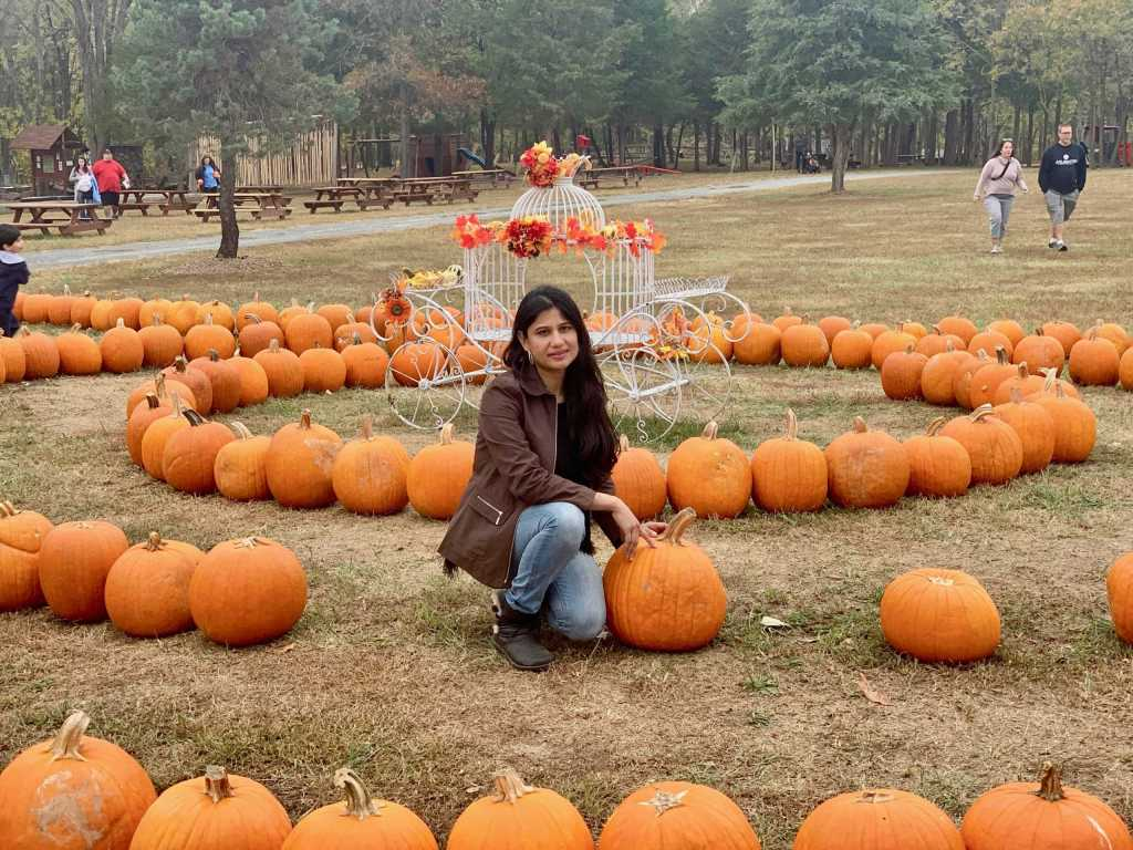 a girl sitting with pumpkins in a farm wearing jeans jacket with jeans and ugg boots