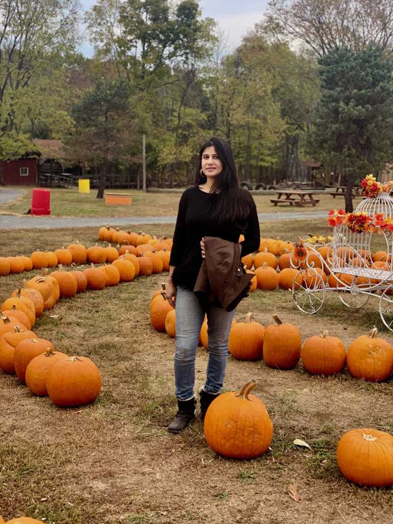 a girl standing in a pumpkin patch showing her style what to wear with jeans