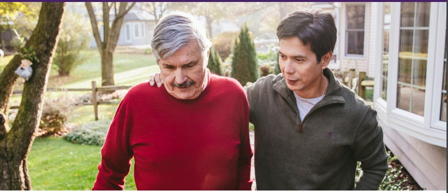 photo of two men, one senior, one younger, walking