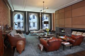 Miestnosť zariadená v industriálnom štýle s mohutnými koženými kreslami