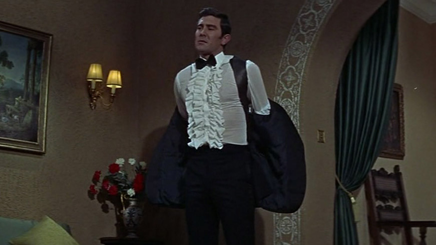 James Bond wearing a ruffled shirt with a tuxedo.