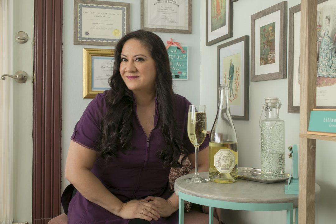 Liliana Aranda in her salon with a bottle and glass of champagne