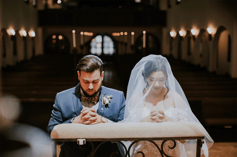 bride and groom praying in church