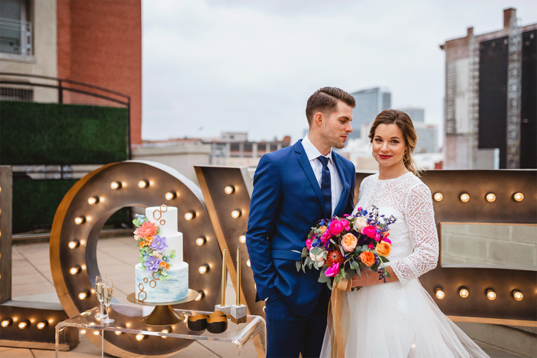 bride and groom in blue suit posing with wedding cake and love marquee letters in lousiville