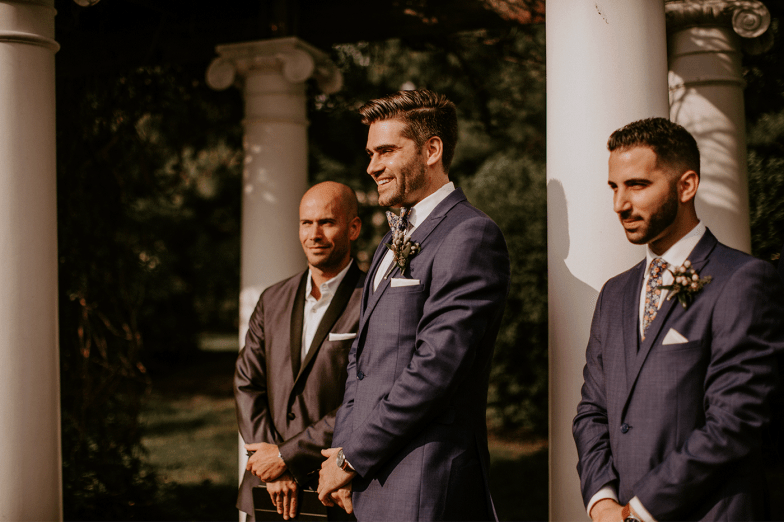 groom in blue suit waiting at alter