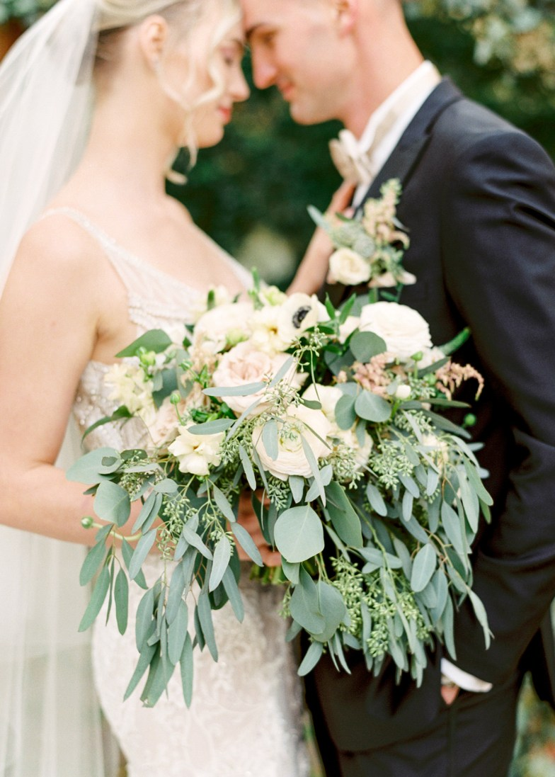 Bride and groom in midnight tuxedo with wedding bouquet