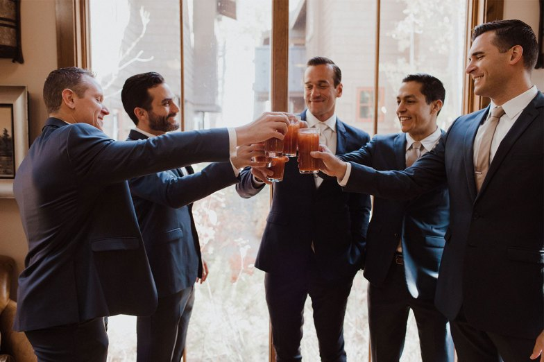 Groom and groomsmen in navy suits toasting