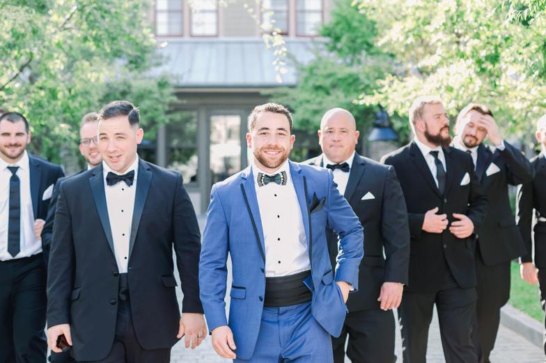 groom in blue tuxedo and groomsmen in black tuxedo