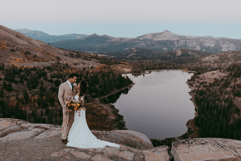 bride and groom in tan suit with mountains