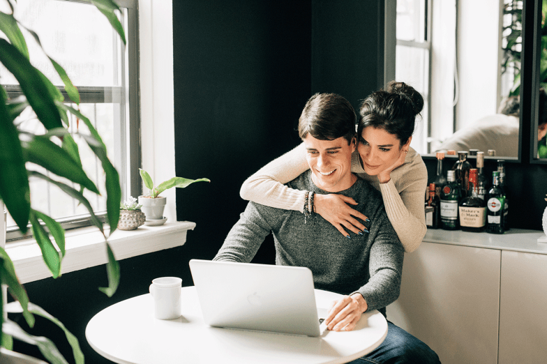 enagged couple looking at computer