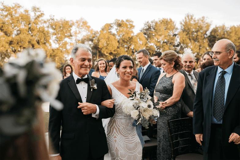 father in black tuxedo walking bride down the aisle