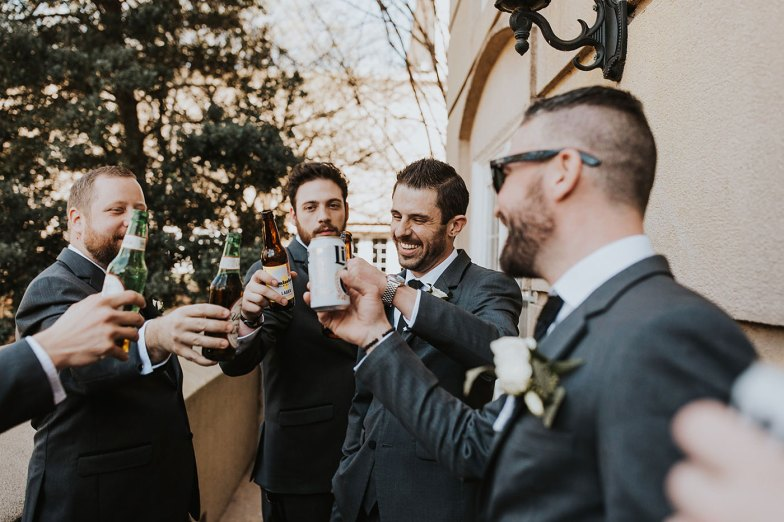 groom and groomsmen in gray tuxedos toasting