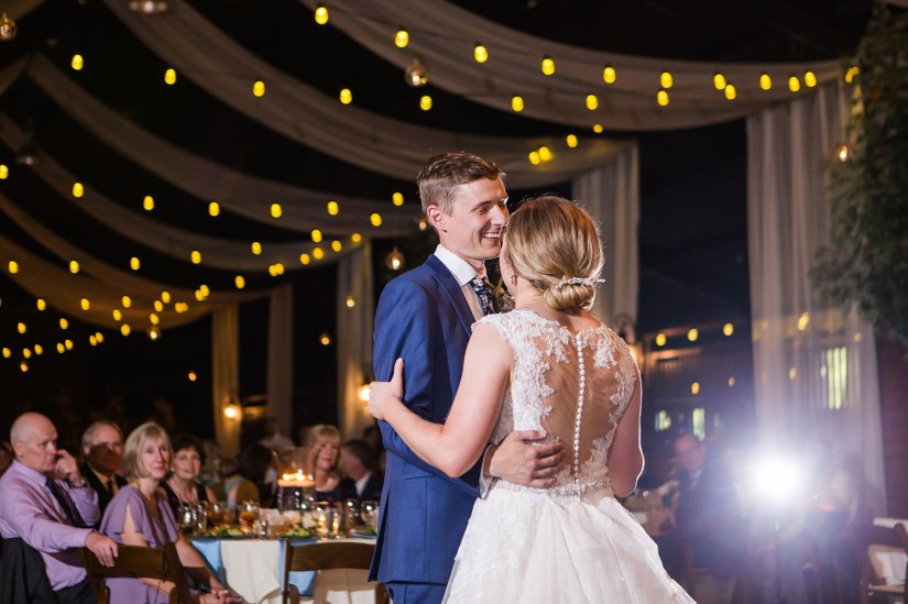 bride and groom in blue suit sharing first dance