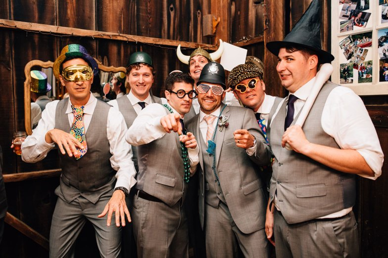 groom and groomsmen in gray suits at wedding reception photo booth