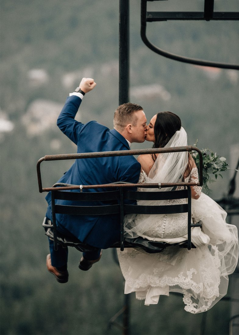 bride and groom in blue suit kissing on ski lift