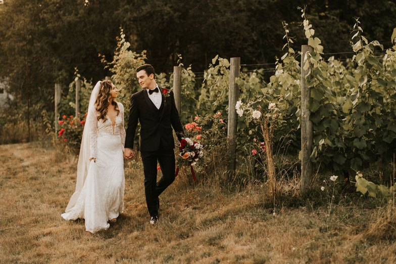 bride and groom in black tuxedo in vineyard
