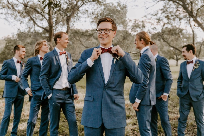 Groom and Groomsmen wearing Generation Tux Mystic Blue Suit with Burgundy Bowtie