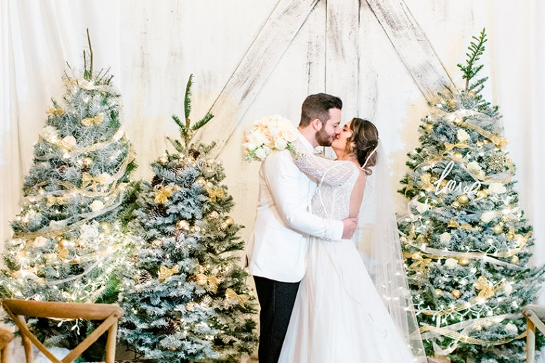 bride and groom in generation tux with christmas trees