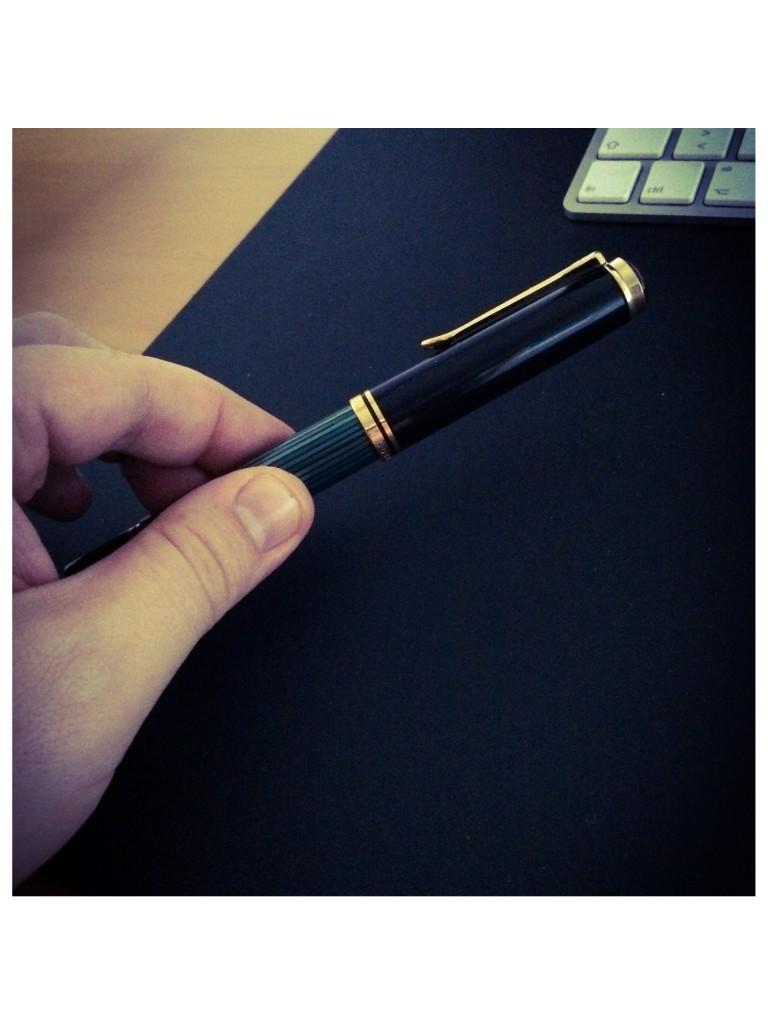 Achtsames Aufheben eines Füllers vom Schreibtisch