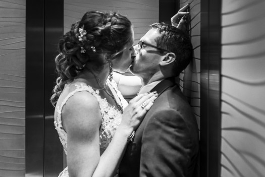 Bride and groom kiss in the elevator.