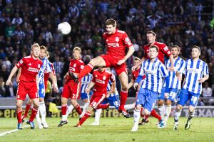 Steven Gerrard jumps to head the ball