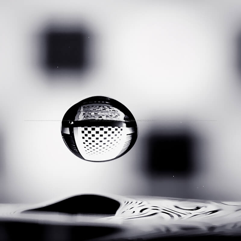 black and white image of a droplet falling and refracting a checkerboard background