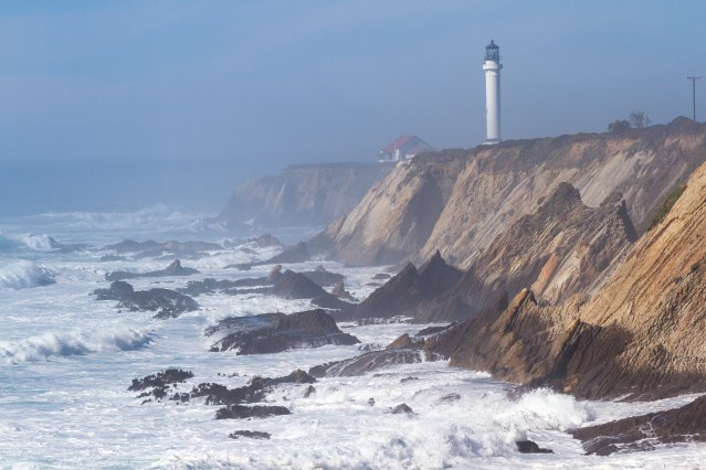 foggy afternoon with rough seas crashing onto the rocks and the Lighthouse at Point Arena in the background