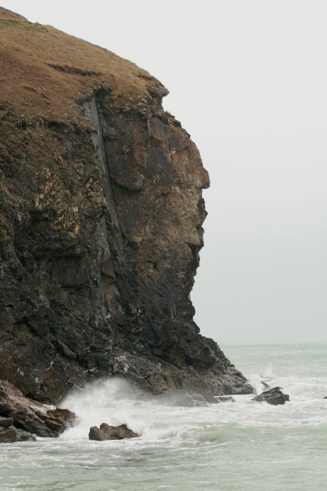 Photograph of a stack just off shore, showing steep cliff faces on all sides