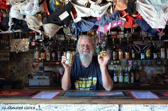Ronnie holds beer & Junior Ranger badge Ronnies Sex Shop Route 62 Barrydale South Africa