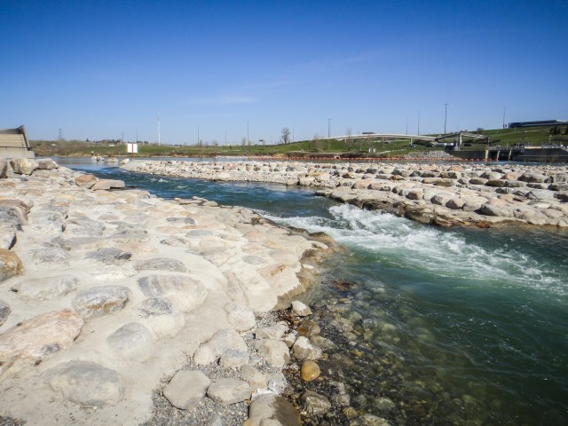 """The new Harvie Passage opened in 2012 - the result of almost 3 years of Bow River renovation near the weir that diverts water into the Western Irrigation District canal. This channel (along the southwest shoreline), is considered a Class II (Intermediate) rapid (i.e.  easy rapids with waves up to one metre high). """"Easy"""" is relative to skill / experience, however. As a result, the Calgary Fire Department has applied to Transport Canada to install the new safety boom upstream from Harvie Passage, in hopes it will prevent those without strong paddling skills from entering the waterway. The Alberta Whitewater Association contends that better signage is a better safety measure. No matter the outcome of the Fire Department's request, it's clear that safety considerations are """"top of mind"""" for all stakeholders."""