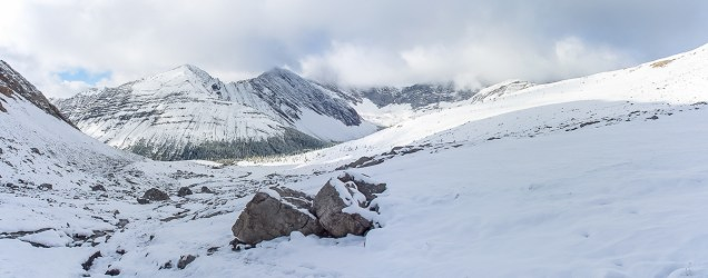 A small creek winds its way down Ptarmigan Cirque, past a snow-covered scree field and the occasional large boulder. The north end of Highwood Ridge is directly across the valley from the creek, and Pocaterra Cirque is across the valley towards the right. Mount Tyrwhitt is obscured by fast-moving clouds. Down at the shoulder of the cirque, there's a nice stand of larch just beginning to turn yellow.