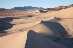 Clusters of sand dunes keep each other company in a quiet desert.