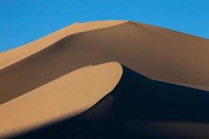 Tall dunes cast shadows over the sand