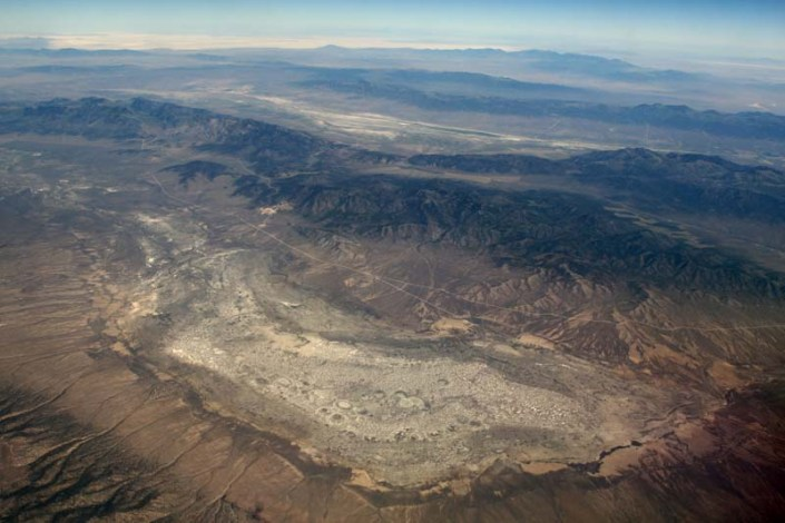 Numerous dry lake beds, or playas, occupy the basins of the Basin and Range Province; they used to be substantial lakes during the wetter climates of the Pleistocene. They are typically very light colored, as they consist of fine-grained clastic material along with salts, deposited during evaporation. A playa occupies the foreground of this photo. Behind it are a series of tilted fault-block ranges. Note the playa in the background. (ID: Dep-27)