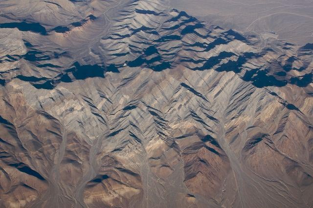 Bare Mountain, a tilted fault block in western Nevada. Bare Mountain, just south of Beatty Nevada illustrates the defining structural style of Basin and Range extension: a tilted fault block. Its southern part consists of faulted Precambrian and Cambrian sedimentary rock. In this photo, one can see a large normal fault separating brown-colored Precambrian-Cambrian Wood Canyon Formation (below) faulted against lighter-colored Cambrian Carrara and Bonanza King Formations. The Carrara and Bonanza King formations show numerous smaller normal faults within them. (ID: IMG_5133)