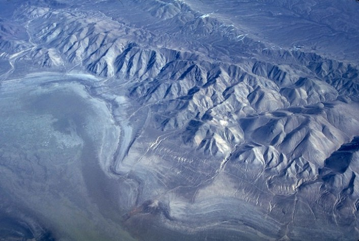 "Numerous dry lake beds, or playas, occupy the basins of the Basin and Range Province; they used to be substantial lakes during the wetter climates of the Pleistocene. These playas contain a record of the lakes' highstands as a series of concentric rings, marking the ancient shorelines, called ""strandlines"". (ID: M-07)"