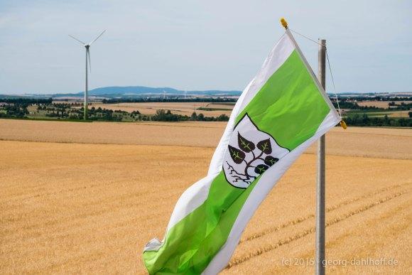 Fahne mit dem Lörzweiler Ortswappen und dem Donnersberg am Horizont - Bild Nr. 201507122719