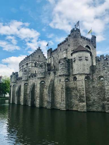 gray concrete castle near body of water during daytime