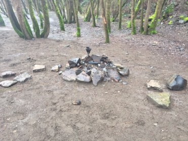 A campfire attests to recent activity along the path leading out of Sellwood Riverfront Park.