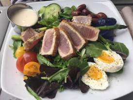 Salad Nicoise: seared ahi tuna, field greens, heirloom cherry tomatoes, soft-boiled eggs, kalamata olives, cucumber slices, asparagus spears and, marinated purple potatoes served with lemon viniagrette dressing.